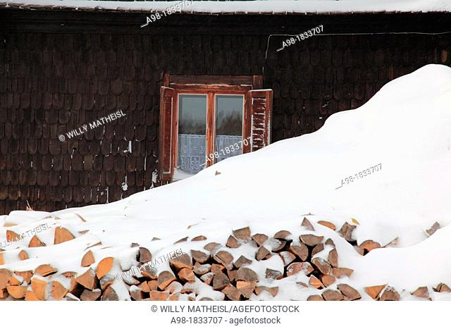 stack of firewood in front of old historic building in winter at the village Prasily, German: Stubenbach, near Susice, Okres Klatovy, Bohemia, Czech Republic