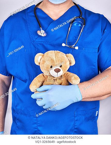 doctor in blue uniform and old latex gloves holding a brown teddy bear, gray background