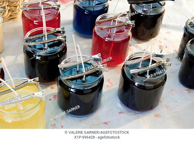 This photo shows a candle maker's work bench with liquid wax in various jars and pins holding the wicks in place, many wax drips are on the tablecloth Photo is...
