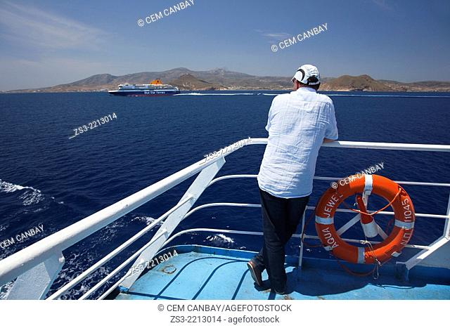 Tourist looking from the ferry deck at the passing ferry, Naxos, Cyclades Islands, Greek Islands, Greece, Europe