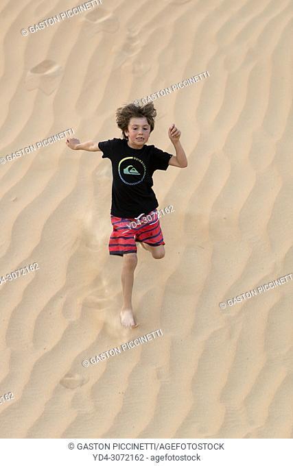 Boy running in the sandune, desert, Dubai, United Arab Emirates