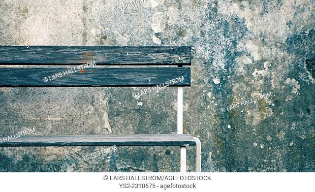 Empty wooden bench with red handprint in front of weathered stone wall