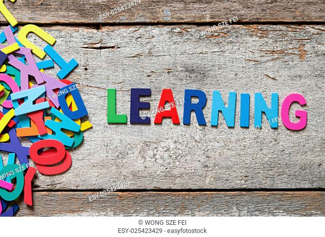 "The colorful words """"LEARNING"""" made with wooden letters next to a pile of other letters over old wooden board"