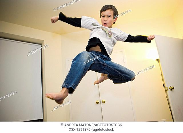 A young boy doing a flying smash kick