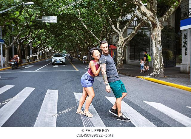 Woman pushing boyfriend on pedestrian crossing, Shanghai French Concession, Shanghai, China