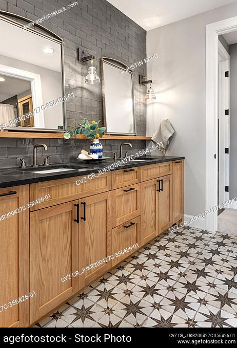 Bathroom in luxury home with double vanity and ornate tile floor