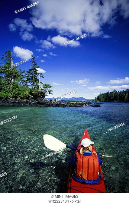 A man in a sea kayak on the clear calm waters off the shore of Ketchikan