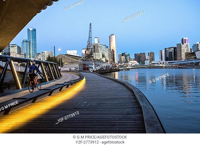 Cyclist on Jim Stynes Bridge, below Wurundjeri Way, with view of Southbank, Melbourne