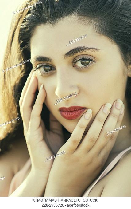 Neautiful young woman hands touching face outdoors