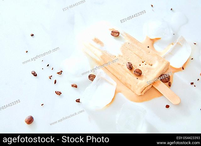 Tiramisu popsicles ice cream with coffee beans on a wooden stick over marble background, top view
