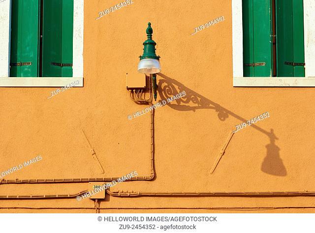 Orange wall green shutters and street lamp with shadow, Burano, Venetian Lagoon, Veneto, Italy, Europe