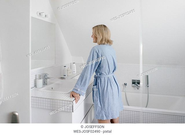 Smiling mature woman looking in bathroom mirror