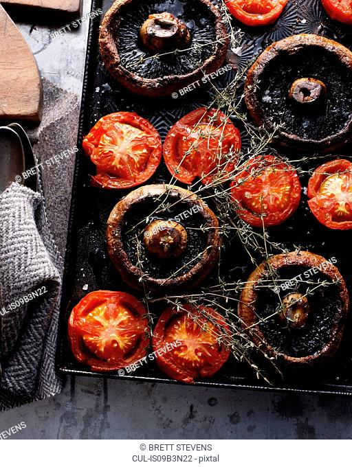 Baked mushrooms and tomatoes on baking tray