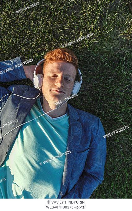 Redheaded young man with headphones lying on grass