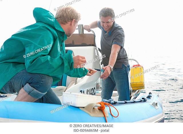 Two young men looking at fishing bait in dinghy