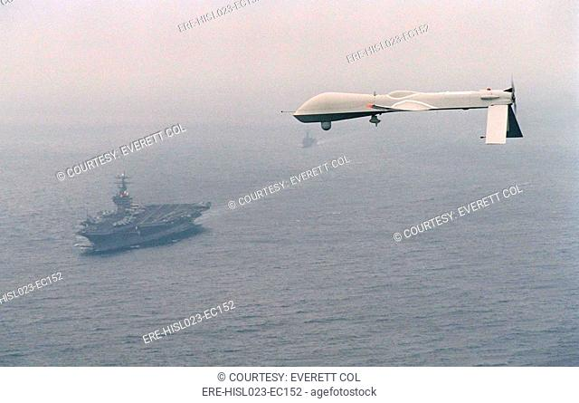 Predator Unmanned Aerial Vehicle flies above the aircraft carrier USS Carl Vinson on a Navy aerial reconnaissance test flight off the coast of California