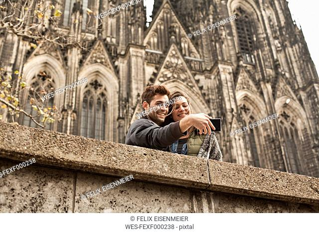 Germany, Cologne, young couple taking a picture in front of Cologne Cathedral