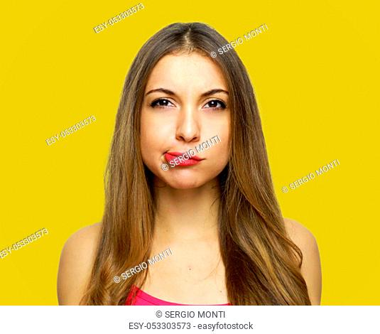 Portrait of a confused young casual girl isolated over yellow background
