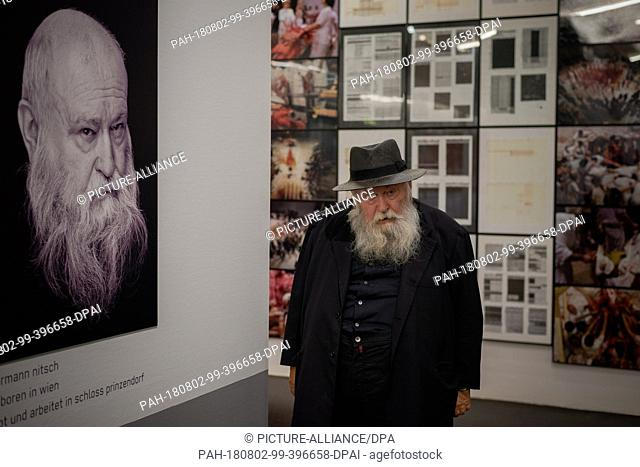 """01 August 2018, Austria, Mistelbach: The Austrian painter and action artist Hermann Nitsch passes by a large portrait in the """"""""nitsch museum"""""""""""