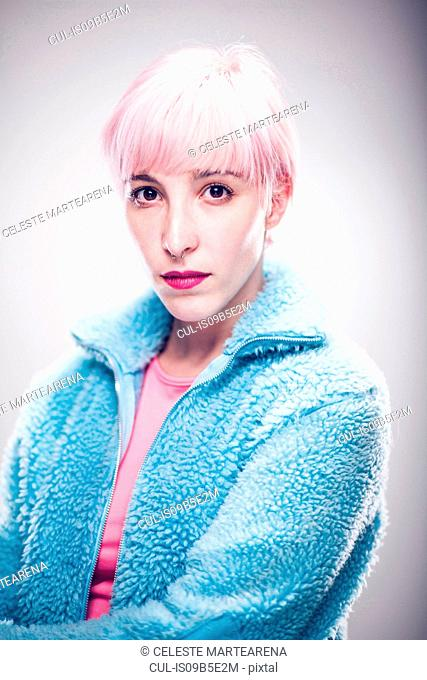 Portrait of young woman with pink hair, pensive expression