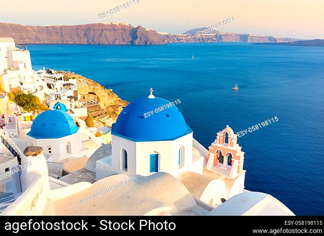 World famous traditional whitewashed chuches and houses of Oia village on Santorini island, Greece. Sunset light