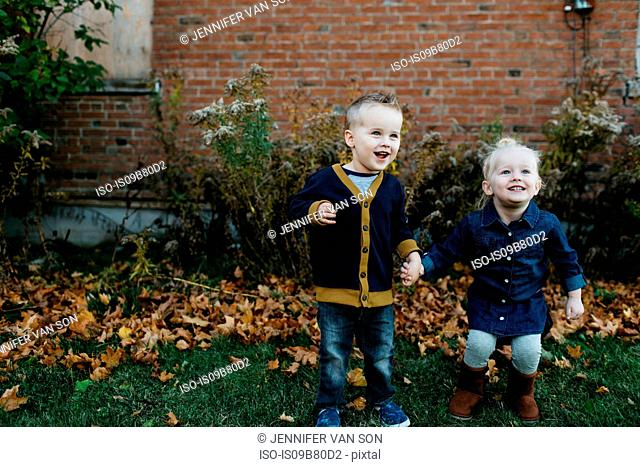 Happy male and female toddler twins holding hands in garden
