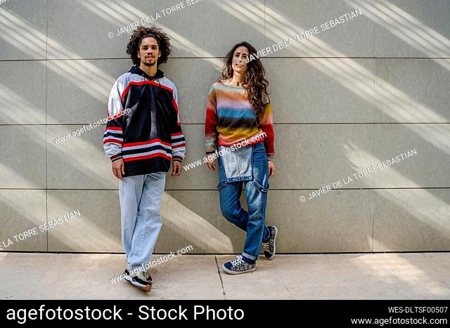 Couple of dancers leaning on a wall and looking at camera