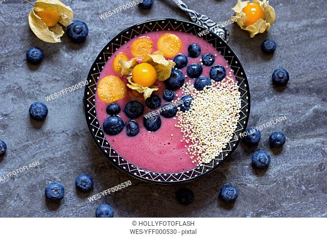 Bowl of blueberry smoothie with popped amarant, blueberries and physalis