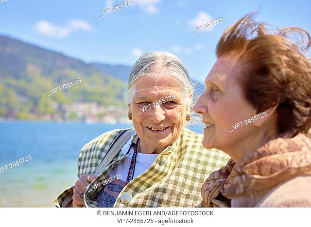 Happy two senior women at lakeside of lake Tegernsee, Bavaria, Germany