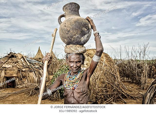 Old Dassanech woman carrying a big pot over her head near Omo river, Omorate, Ethiopia