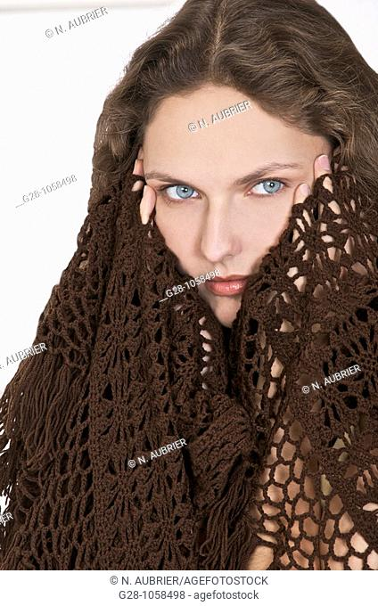 young woman in a brown shawl,holding her temples because of  a headache