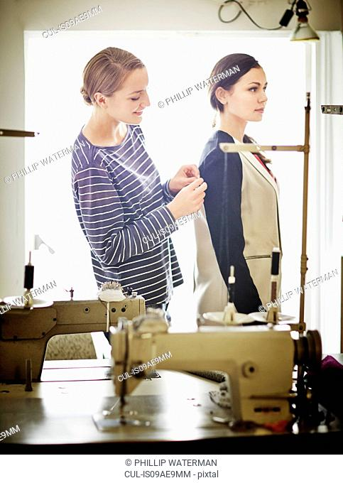 Seamstress adjusting woman's jacket
