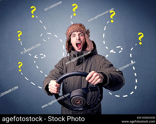 Young man holding black steering wheel with question marks around him