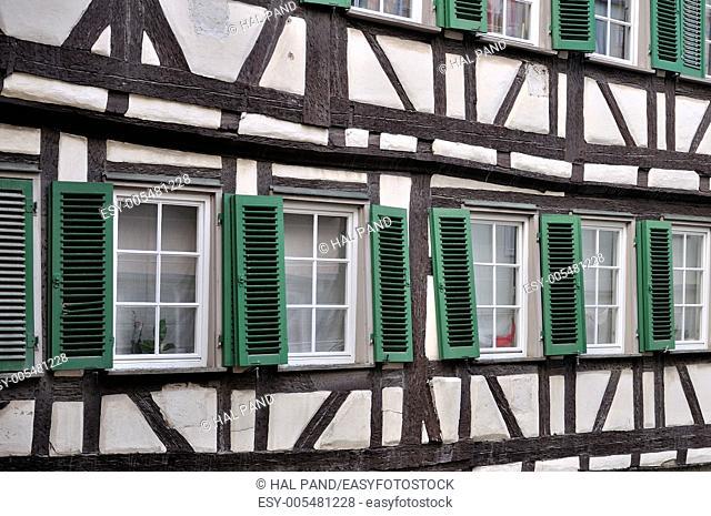 green shutters on wattle facade, tubingen, detail of misaligned windows on old wattle building in city center