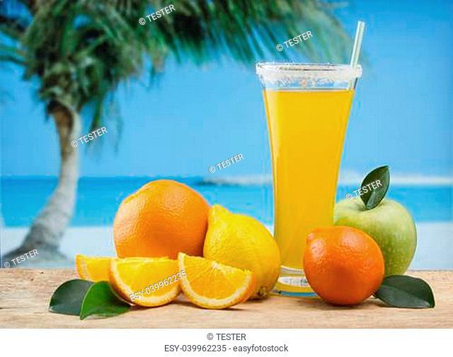 Glass of orange juice on a beach table
