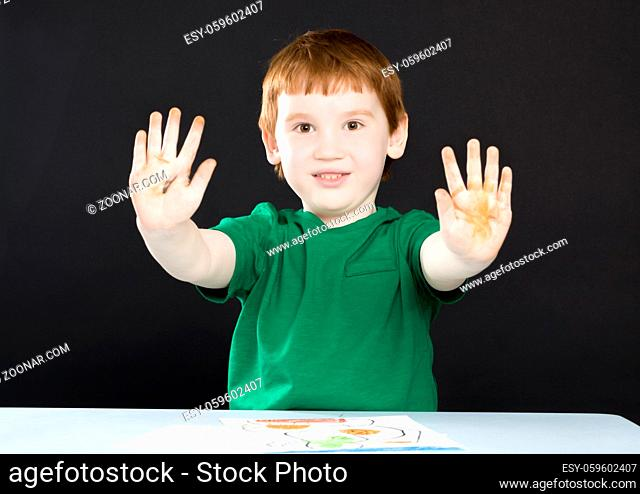 a little red-haired boy in a green shirt painted a picture and showing dirty hands from pencils