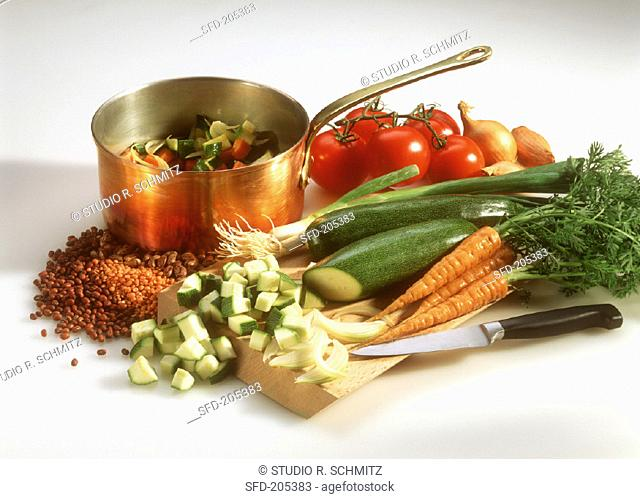Various vegetables, kitchen knife & pan of diced vegetables