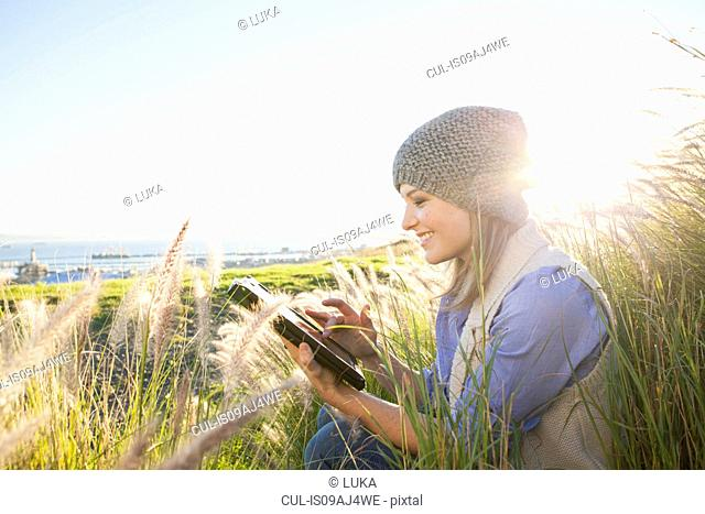 Young woman using digital tablet in fields