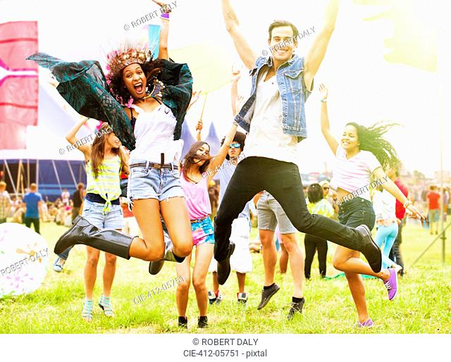 Portrait of enthusiastic friends jumping and dancing at music festival