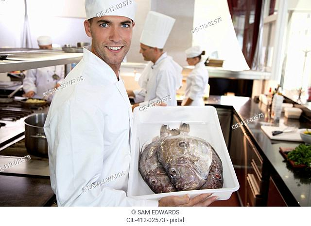 Chef carrying tub of fresh fish in restaurant kitchen