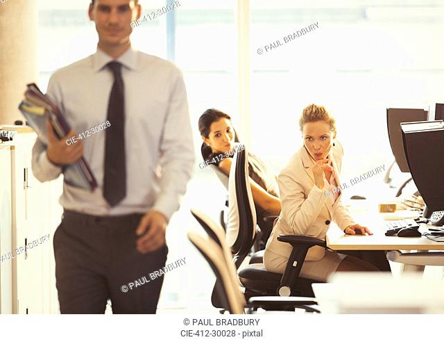 Businesswomen checking out passing businessman in office