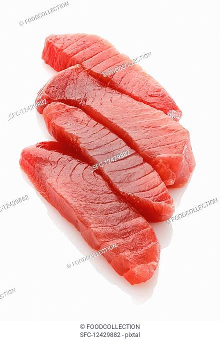 Four fresh tuna fish steaks on a white surface
