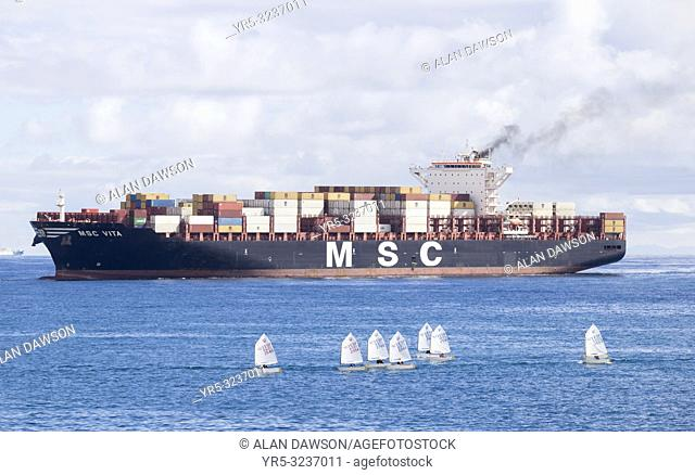 Las Palmas, Gran Canaria, Canary Islands, Spain. Container ship passing close to small dinghies as it enters Las Palmas port