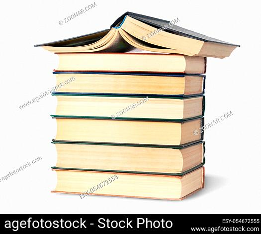 Stack of six old books with an open top rotated isolated on white background
