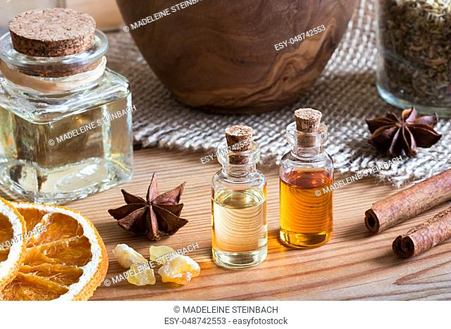 Bottles of essential oil with star anise, cinnamon, frankincense and dried orange slices