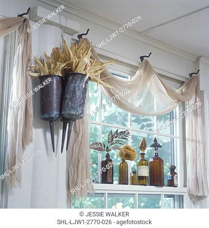 WINDOW TREATMENTS: Unique, Scrim a net like fabric valance, old coat hooks serve as drape points for scarf valance, copper funeral urns on left filled with...