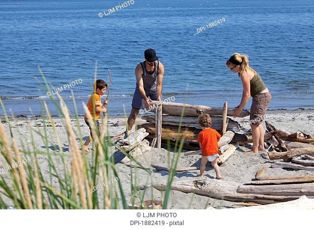 A Family Piles Driftwood On The Beach, Langley, British Columbia, Canada
