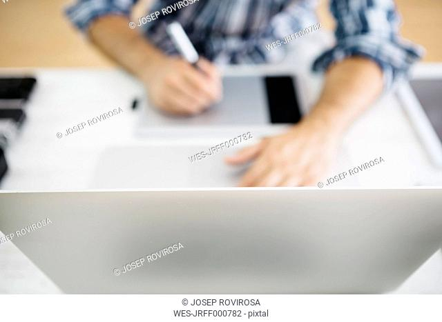 Man working at desk with laptop and graphic tablets, partial view