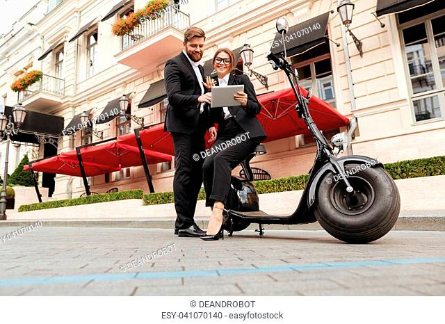 Full length portrait of a smiling young couple in smart clothes standing and using tablet computer on a city street while leaning on a motor bicycle