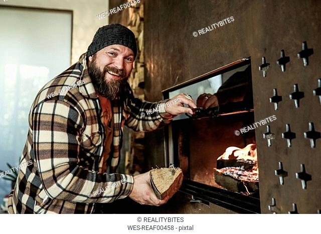 Portrait of bearded man in front of fireplace at home